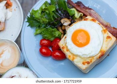 Hot french toasts croque madame with ham, melted emmental cheese and fried sunny side up egg. Croque-madame with beautiful fried eggs, bread and ham cheese. Croque madame sandwich on the table.