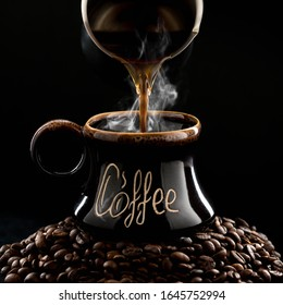 """Hot, fresh, brewed coffee is poured into a dark brown mug with the inscription """"coffee"""" standing on a hill of coffee beans. Black background. Square."""