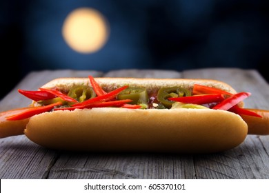 Hot fresh chili hot dog with salsa sauce on wooden table , moon background
