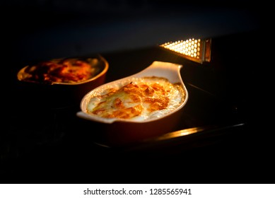 Hot and fresh delicious potato gratin with cream and cheese inside the oven