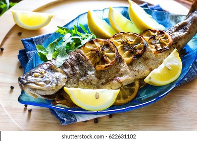 Hot fresh savory grilled whole trout barbeque with fresh herbs and lemon, served black pepper and arugula salad leaves on blue plate wooden background top view close up