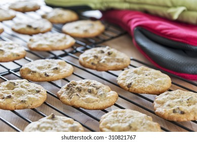 Hot freshly baked chocolate chip cookies cooling on wire racks.  A selective focus and shallow depth of field was incorporated on purpose in this image.