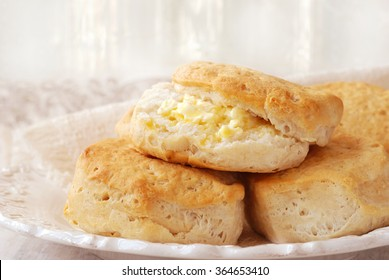 Hot freshly baked homemade biscuits.  Closeup with shallow dof  (de-focused sunlit window  with sheer curtains in background)