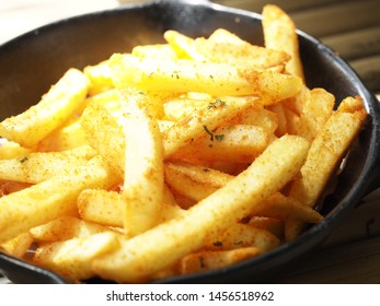 Hot fried French fries in a black plate on a bamboo table with a sauce for eating