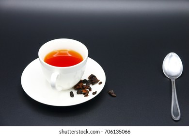 Hot Fruit tea  in White Ceramic Mug and spoon on dark background