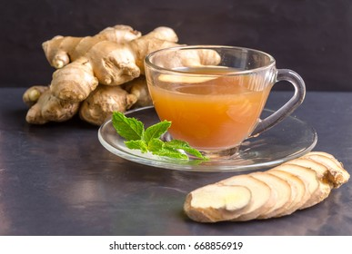 Hot Ginger juice  and mint with root and slices of ginger  on black stone background. Hot Ginger juice can helps warming body.