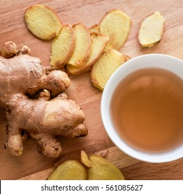 Hot Ginger tea cup with root and slices of ginger on wood cutting board background. Ginger tea in cold weather helps warming human body.