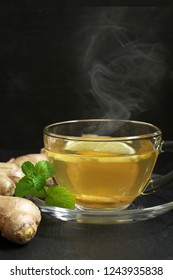 Hot ginger tea with lemon in glass cup, ginger root and mint on slate against black background.