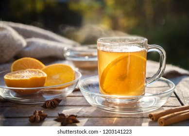 hot ginger tea with orange slices and spices on a wooden table in the sun, healthy drink against cold, copy space, selected focus, narrow depth of field