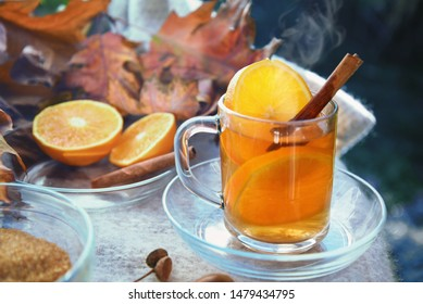 hot ginger tea with orange slices and cinnamon in a glass cup on a blanket and some red autumn leaves, selected focus, narrow depth of field
