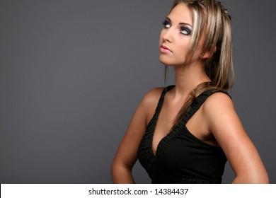 Hot girl,  blond model in black dress posing on grey background