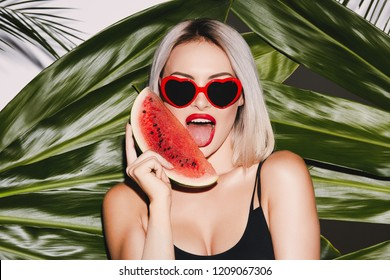 Hot girl with blonde hair wearing black swimming suit and sunglasses standing at palm background, sexy model, posing with watermelon, red lipstick, close up portrait.