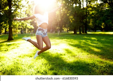 Hot girl with sporty sexy body jumps in a green park with sun flares