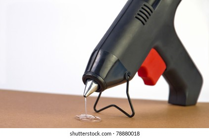 a hot glue gun with glue dripping out of nozzle