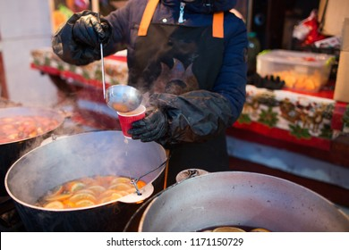 Hot gluhwein or mulled wine in a cauldron at fair, local treat, warm and spicy. A hot wholesome traditional citrus drink on fair. Vitamins in the winter festival. Christmas market.