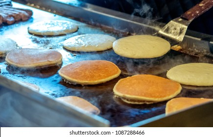 hot golden pancakes cook on a metal griddle at a big pancake breakfast
