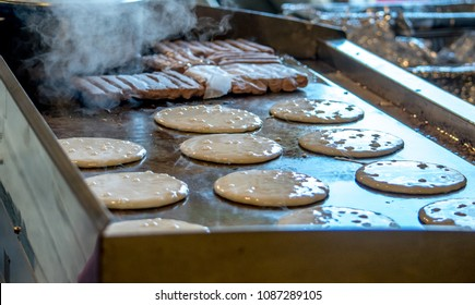hot golden pancakes and sausage links cook on a metal griddle at a big pancake breakfast