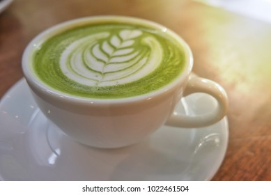 Hot green tea latte beautiful pattern, White cup on wood table in coffee shop