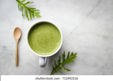 Hot green tea latte  with green leaves and wooden spoon