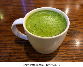 Hot green tea latte on the wood table
