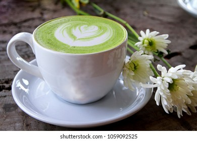 Hot green tea latte with white flower on wooden background.