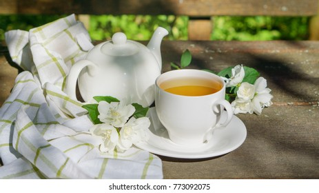 Hot green tea in a teapot and cup with a branch of jasmine flowers blossom  and white towel on rough rustic brown wooden background.  Nature healthy slow life concept.