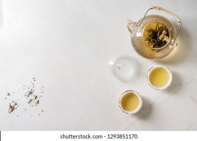 Hot green tea in two traditional chinese clay ceramic cup and glass teapot over white marble background. Flat lay, space