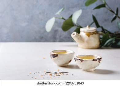 Hot green tea in two traditional chinese clay ceramic cup and teapot standing on white marble table. With green branch at background.