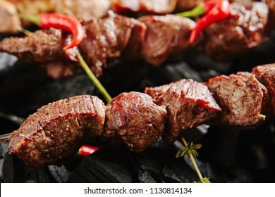 Hot Grilled Beef Kebab or Barbecue Shashlik on Charcoal Background with Herbs and Spices Closup. Macro Photo of Skewered and Grilled Cubes of Veal Meat Decorated with Spicy Red Pepper and Thyme