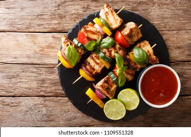 Hot grilled chicken kebab skewers with colorful vegetables with sauce, basil and lime closeup on the table. Horizontal top view from above