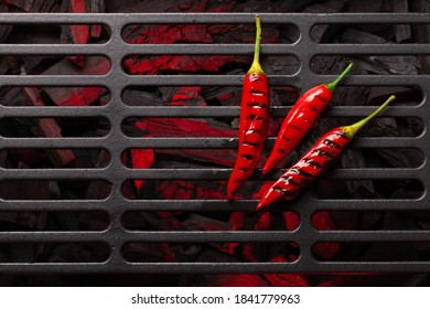 Hot grilled chili pepper on grill. Top view flat lay with copy space