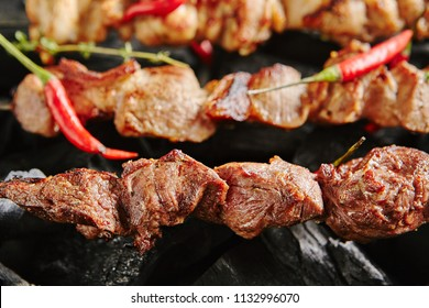 Hot Grilled Lamb Kebab or Barbecue Shashlik on Charcoal Background with Herbs and Spices Closup. Macro Photo of Skewered Grilled Cubes of Mutton Meat Decorated with Spicy Red Pepper and Thyme