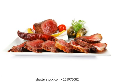 hot grilled meat and vegetables served on plates
