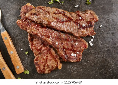 Hot Grilled Whole Gaucho Steak on Black Stone Background. Fresh Juicy Medium Rare Beef Grillsteak. Barbecue Meat Top View Close Up