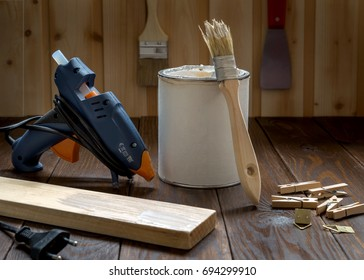 A hot gun and a can of paint and a brush in the workshop on a dark table.