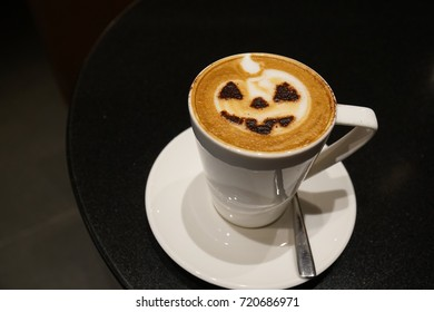 Hot Halloween coffee in the white cup with scary pumpkin face foam