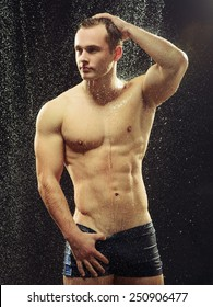 Too hot to handle. Side view portrait of young sexual gay man taking a shower with water drops on his muscled body against black background