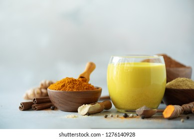 Hot healthy drink. Turmeric latte, golden milk with turmeric root, ginger powder, black pepper over grey background. Copy space. Spices for ayurvedic treatment. Alternative medicine concept