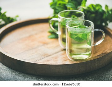Hot herbal mint tea drink in glass mugs over wooden tray with fresh garden mint leaves, selective focus, copy space