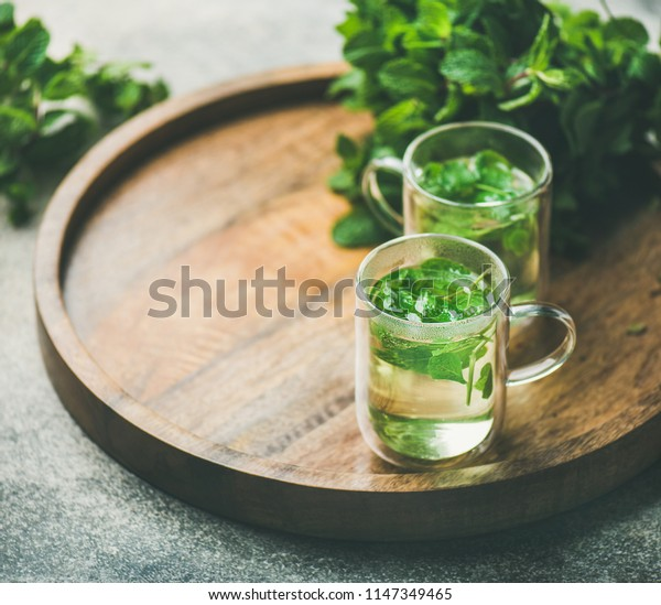 Hot herbal mint tea drink in glass mugs over wooden tray with fresh garden mint leaves, selective focus, copy space, horizontal composition