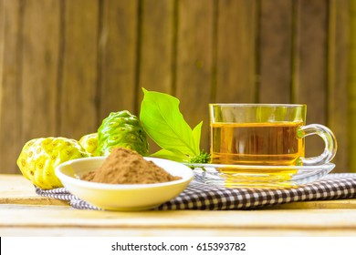 Hot herbal noni,Noni herbal juice with noni fruit and noni powder on wooden background.