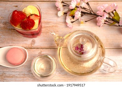 Hot herbal tea drink, Teapot and glass cups with blooming tea rose flower inside served with sweet dessert, Strawberry Mousse Cheese Cake, on white lace placemat putting on wooden table