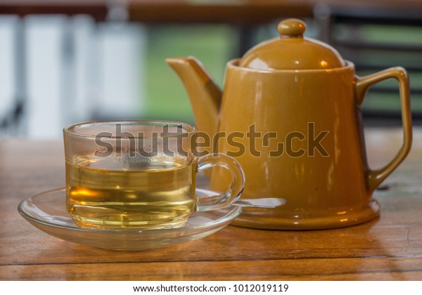Hot Herbal Tea in Glass with Yellow Teapot served on Wooden Table against Green Garden Blurred Background. Concept of Morning Booster, Afternoon Tea Break, Holidays, or Relaxing Time Outside