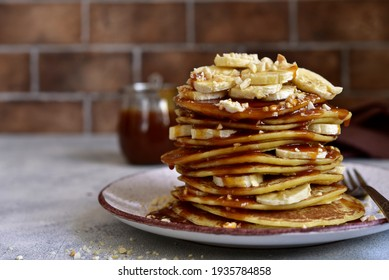 Hot homemade banana pancakes with caramel sauce and nuts  on a plate.