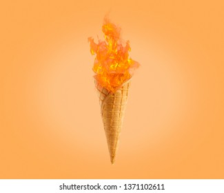 Hot ice cream fireball in horn waffle, flame goes from flamethrower, yellow-orange color background  - Image