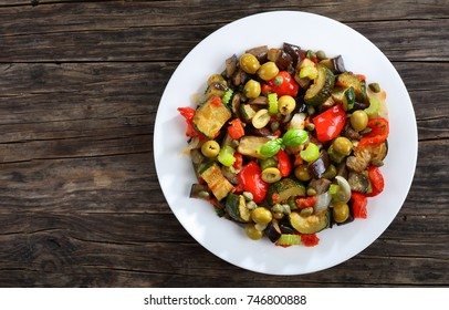 hot Italian Caponata with vegetables, green olives, capers, celery and herbs on white plate on dark wooden table, view from above