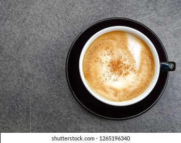 hot Italian cappuccino black cup on grey table background, top view