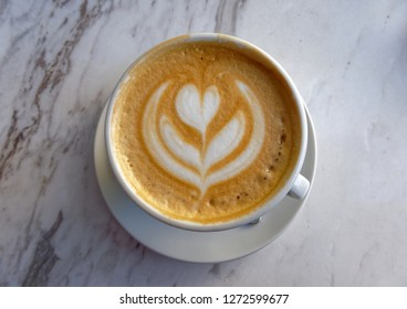 hot Italian cappuccino coffee on marble table background, top view