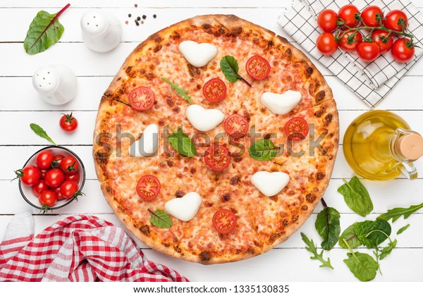 Hot Italian Pizza With Heart Shaped Mozzarella, Tomatoes, Cheese And Green Salad Leaf. Top View. Food Flat Lay