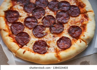Hot italian pizza with mozzarella and pepperoni sausage close-up